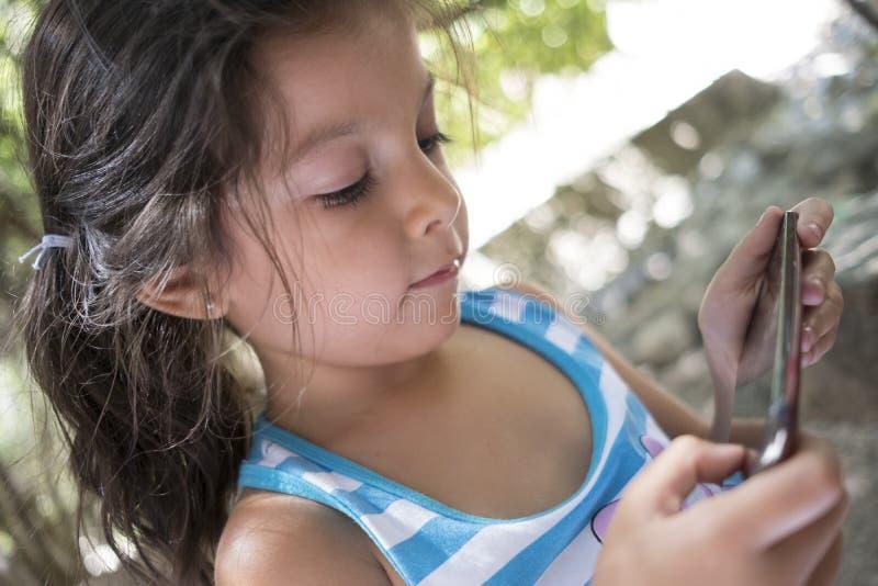四岁看智能手机的女孩 免版税库存图片