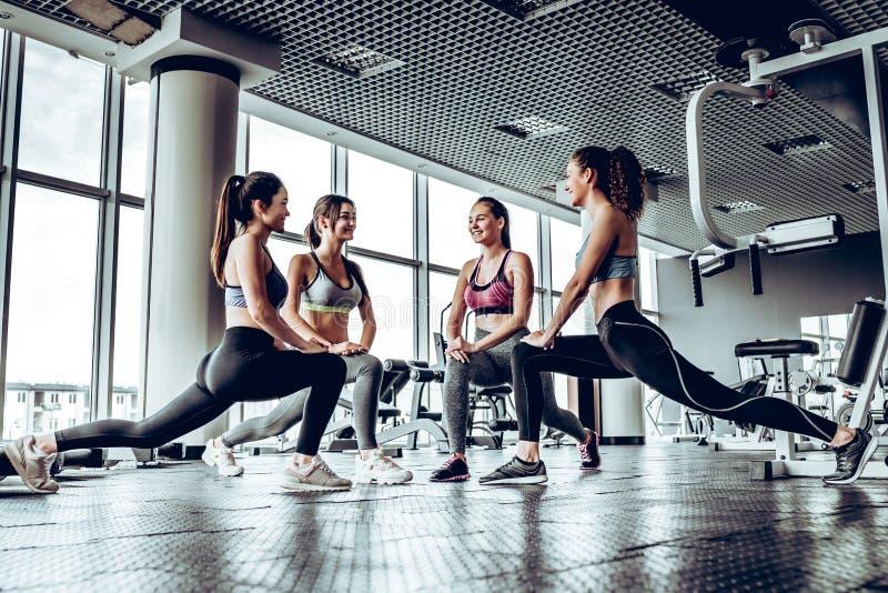 四执行低放射性微尘的运动妇女在健身房与全景窗口背景 库存图片
