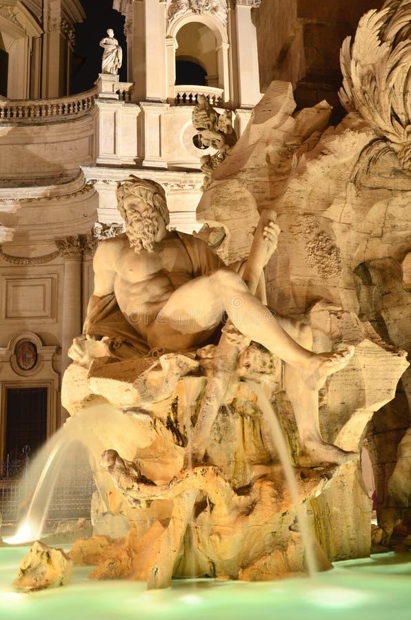四条河的美丽的喷泉在纳沃纳广场的夜之前在罗马,意大利 免版税库存照片