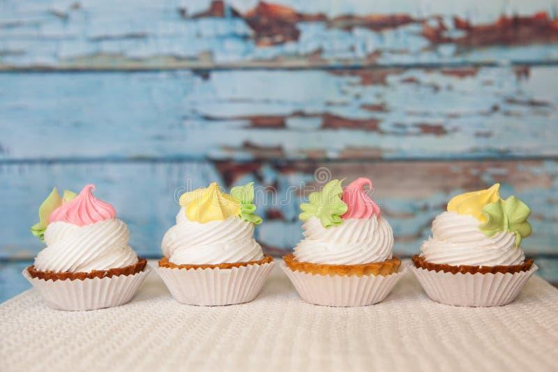 四桃红色和在蓝色背景的黄色杯形蛋糕与拷贝空间,点心食物 免版税库存图片