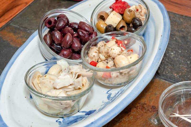四碗各种各样的橄榄和烂醉如泥的开胃菜前晚餐开胃小菜的 库存照片