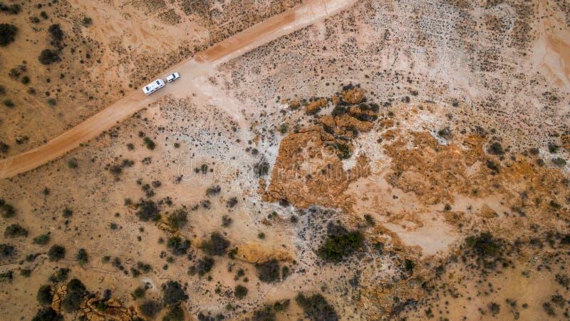 四轮驱动的车和大有蓬卡车空中veiw在沙漠 图库摄影