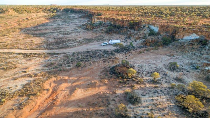 四轮驱动的车和大有蓬卡车鸟瞰图在峭壁附近野营 免版税库存图片