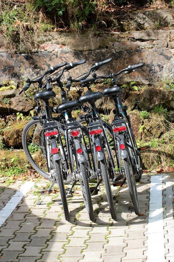 四辆相同黑自行车在一个晴天 健康生活方式 滑雪在新鲜空气的山 免版税库存照片