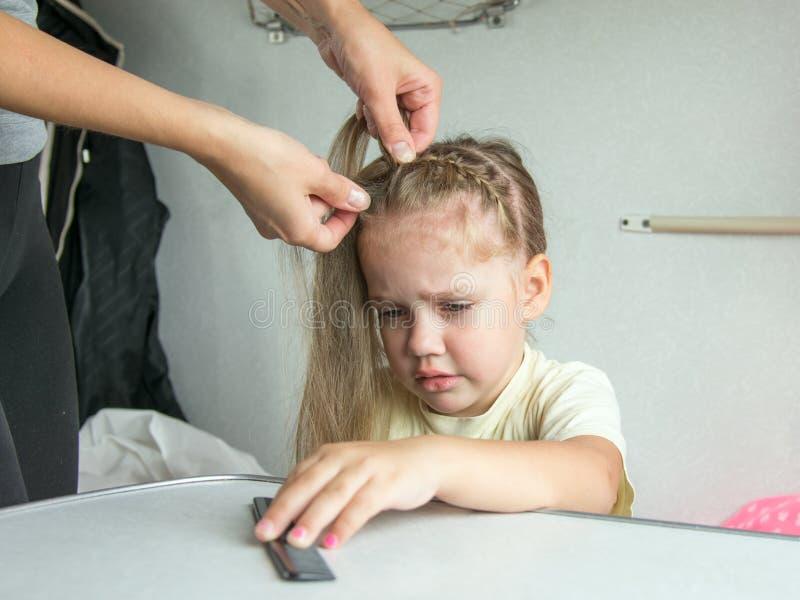 四年女孩在痛苦中哭泣,当梳她的头发的我的母亲 免版税库存照片