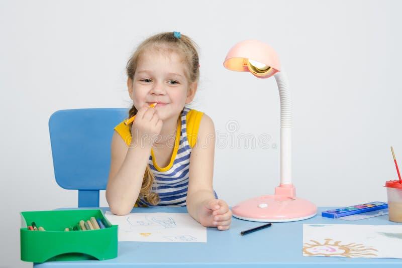 四年女孩设想了并且投入了铅笔到他的嘴唇 库存图片