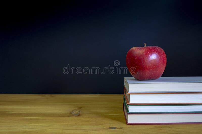 回到与书的学校背景在书桌 库存照片