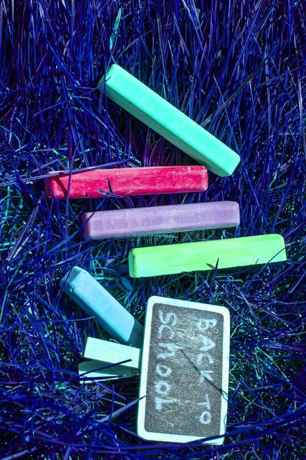 回到与五颜六色的霓虹色的蜡笔的学校背景,在紫色发光的背景 平的位置,顶视图,拷贝空间 免版税库存照片