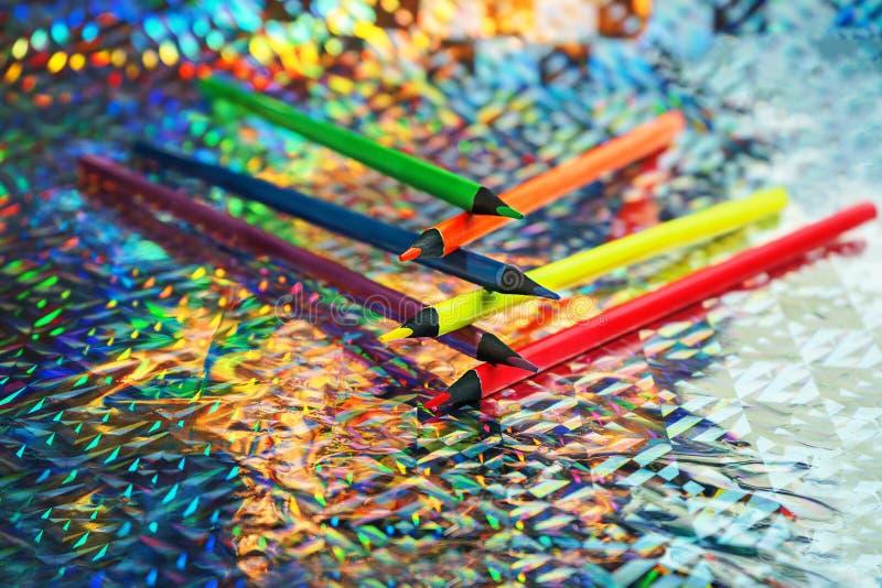 回到与五颜六色的霓虹颜色铅笔的学校背景在全息照相的箔背景 库存图片
