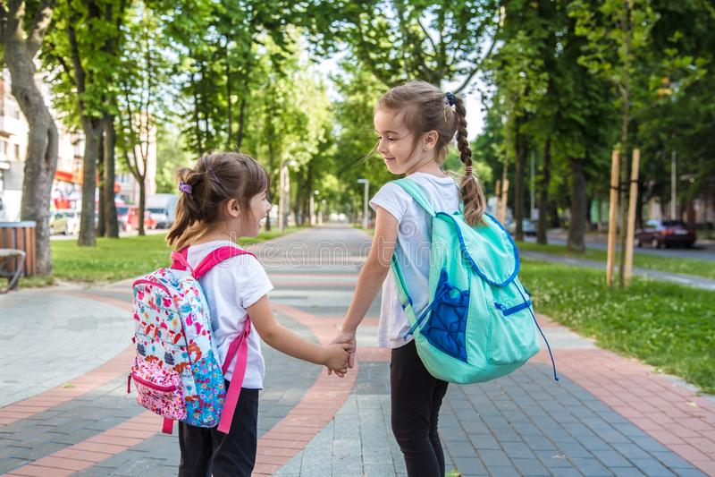 回到与女孩孩子的学校教育概念,小学生,去运载的背包分类 免版税库存照片