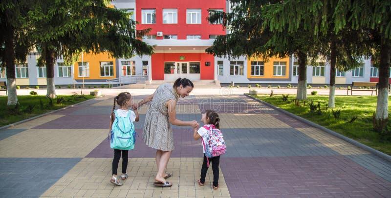 回到与女孩孩子的学校教育概念,小学生,去运载的背包分类 免版税图库摄影