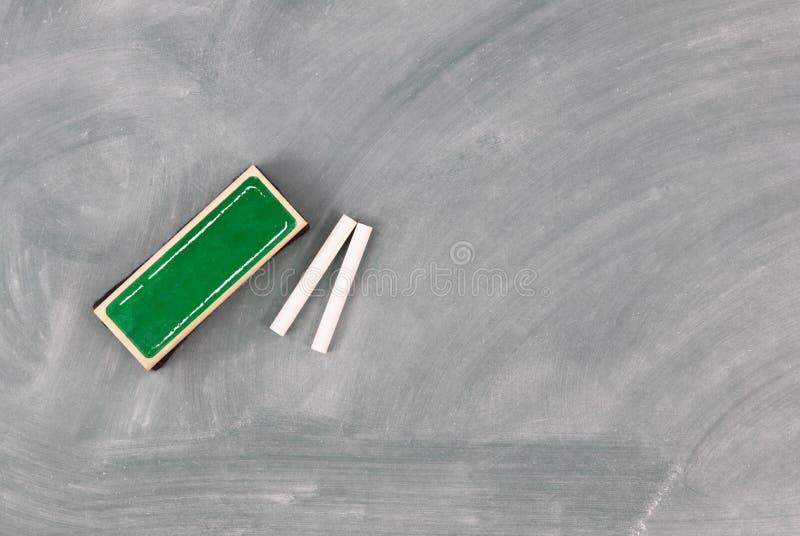 回到与绿色黑板的学校概念加上橡皮擦和白垩 库存照片