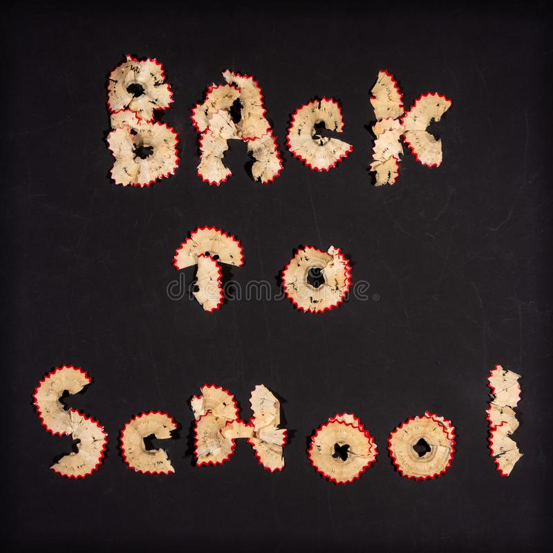 回到从铅笔削片的学校课文在黑黑板背景 库存图片