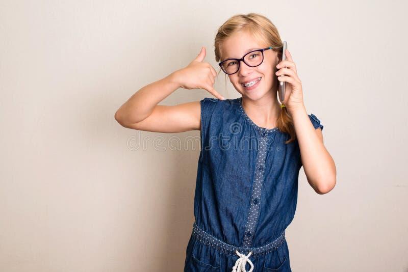 回到告诉我 有显示电话我的智能手机的俏丽的青少年的女孩 免版税库存照片