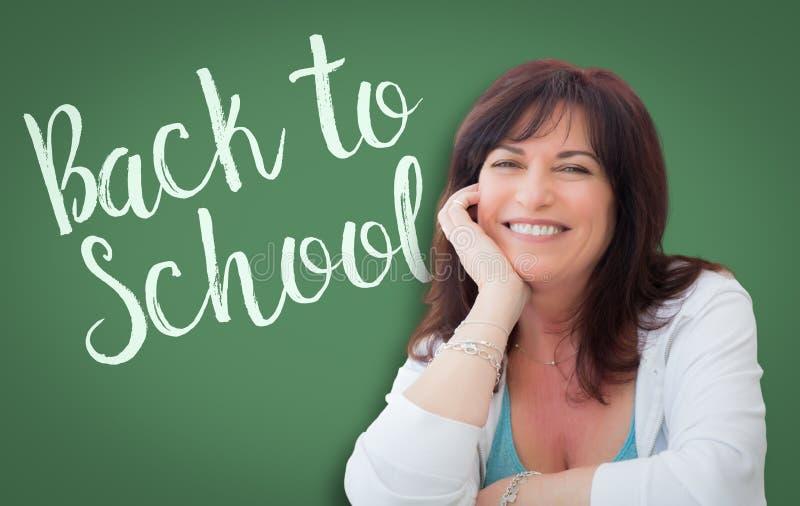 回到在妇女、老师或者图书管理员后的绿色黑板写的学校 免版税库存图片