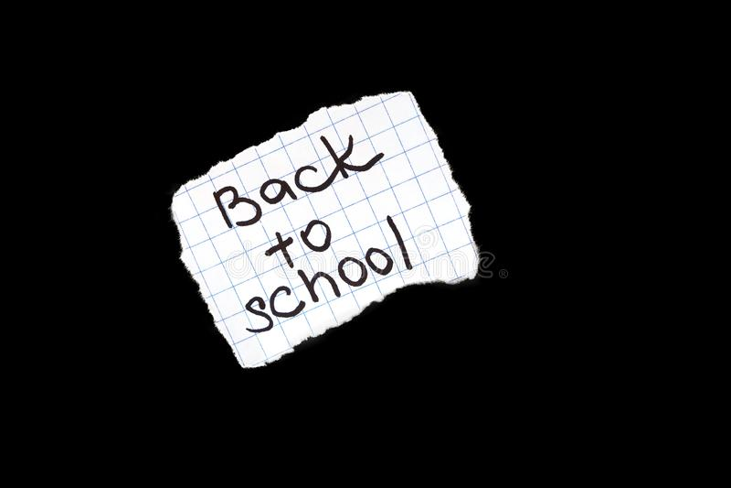 回到在纸的学校题字在黑背景 库存照片