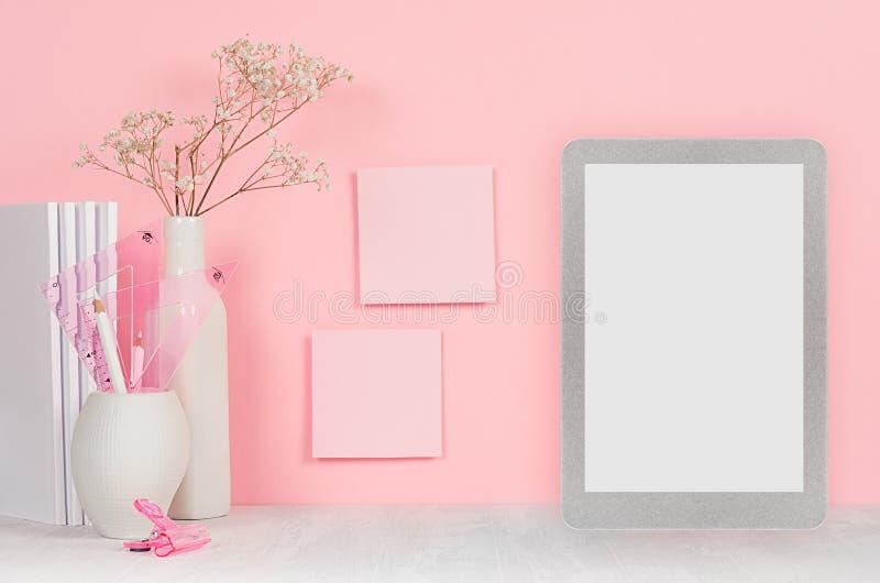 回到女孩`的s学校背景-白色文具,删去片剂计算机和贴纸在软的桃红色墙壁和白色木书桌上 免版税库存照片