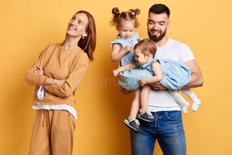 回到她的丈夫和她的小女儿的愉快的年轻母亲身分 免版税库存照片