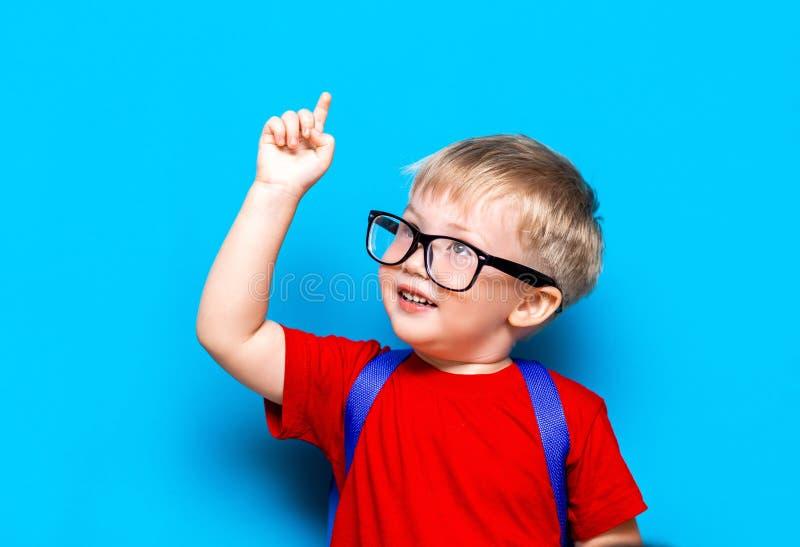 回到学校一级小辈生活方式 红色T恤杉的小男孩 演播室微笑的男孩照片画象的关闭玻璃的 免版税图库摄影