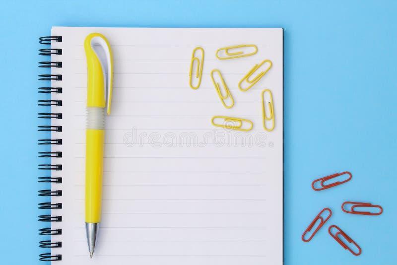 回到学校创造性的概念 与黄色笔的在蓝色背景的笔记薄和夹子 平的位置的顶视图 库存照片