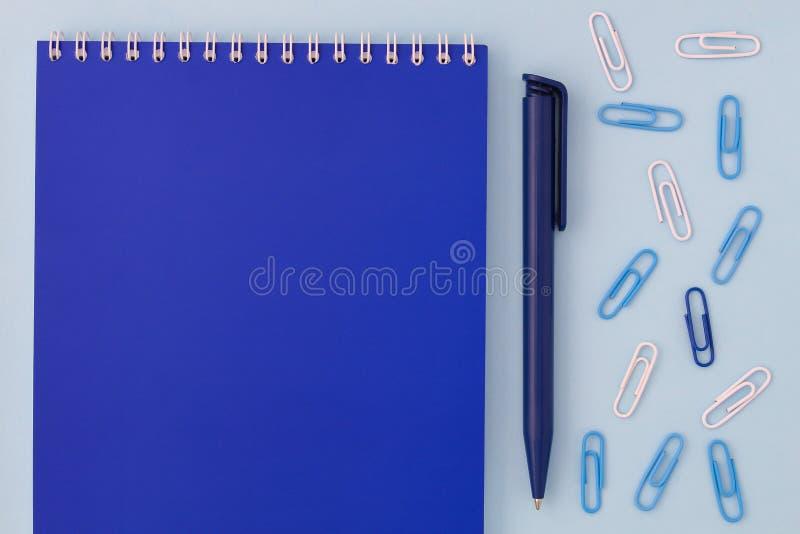 回到学校创造性的概念 有笔的蓝色笔记本和在平的位置的一张蓝色背景顶视图的纸夹 男孩样或 免版税图库摄影