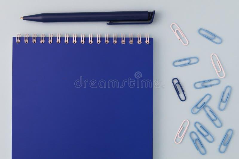 回到学校创造性的概念 有笔的蓝色笔记本和在平的位置的一张蓝色背景顶视图的纸夹 男孩样或 免版税库存图片