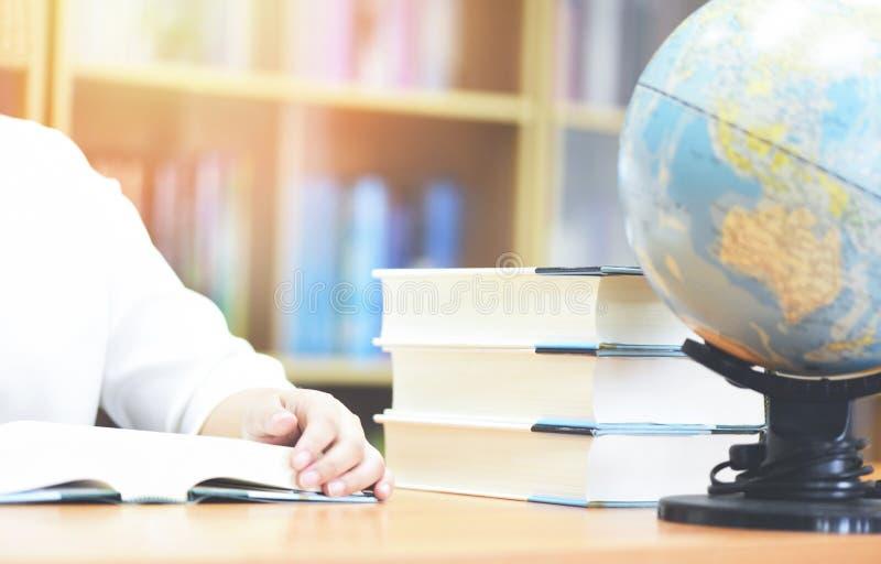 回到学校和商业研究全球性世界-年轻女人读一本书的学生校园的教育概念在有书的图书馆里 图库摄影
