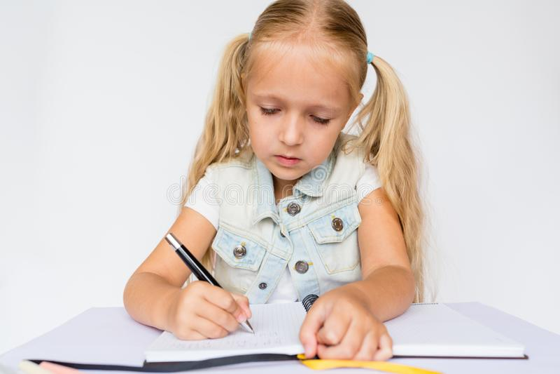 回到学校和幸福时光 儿童候宰栏和写在笔记本在白色背景 做家庭作业的孩子 大模型, 库存图片