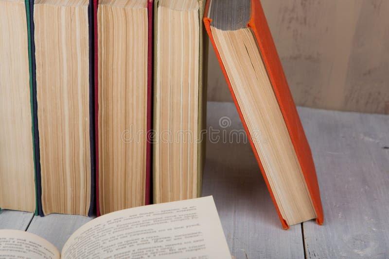 回到学校和教育概念-在白色木桌上的堆五颜六色的精装书书在棕色背景 免版税库存照片