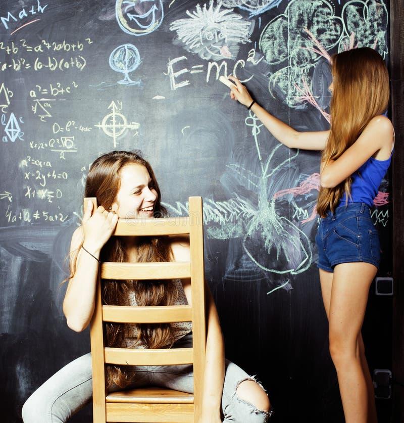 回到学校在暑假以后,两个青少年的女孩在有一起被绘的黑板的教室 免版税库存图片