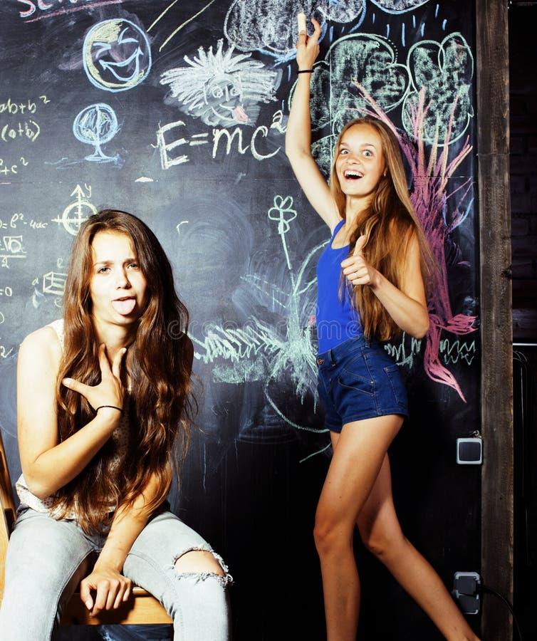 回到学校在暑假以后,两个青少年的女孩在有被绘的黑板的教室 库存照片