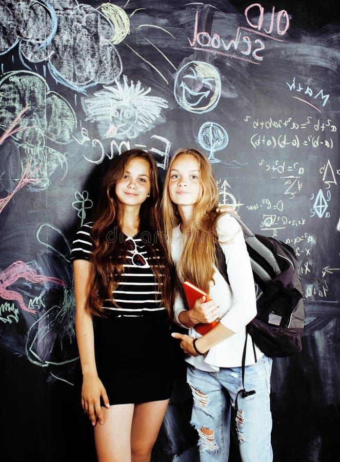 回到学校在暑假以后,两个青少年的真正的女孩在有一起被绘的黑板的教室,生活方式 图库摄影