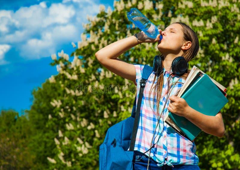 回到学校学生少年女孩喝从瓶的水和佩带背包的对负书和笔记本 库存照片