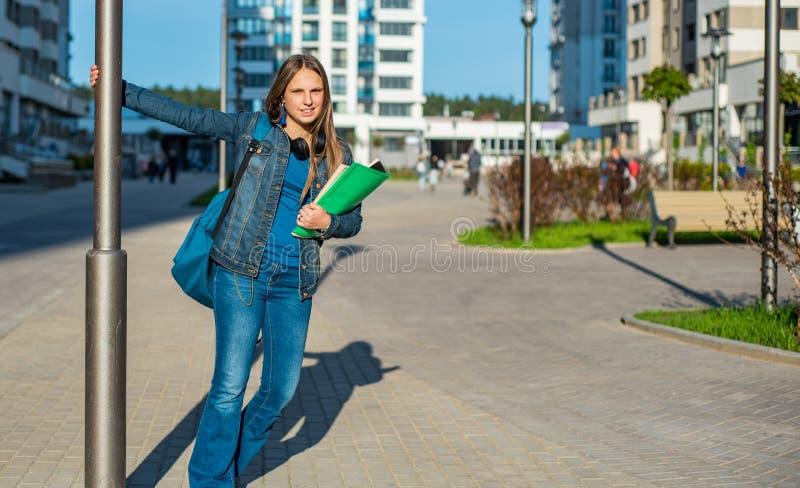 回到学校学生拿着书和笔记本的少年女孩佩带背包 年轻少年深色的美国兵室外画象  免版税库存照片
