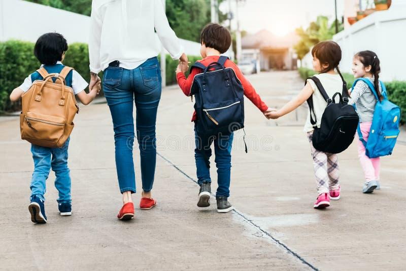 回到学校学生母亲小组去的学校一起 父母送小男孩和女孩头等学期期限的与 库存照片