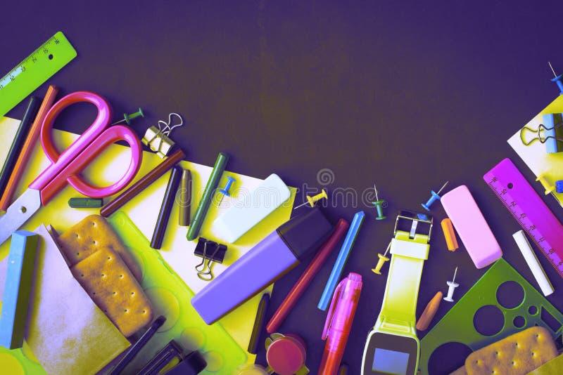 回到学校手表粉笔线在黑背景的曲奇饼文具的超现实主义概念 图库摄影