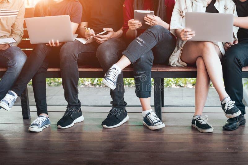 回到学校教育知识学院大学概念的青年人利用计算机和片剂、教育和technolo 库存图片