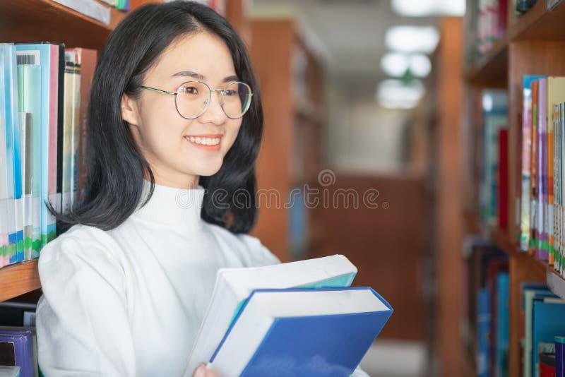 回到学校教育知识学院大学概念,拿着她的书的美丽的女性大学生愉快地微笑 免版税图库摄影