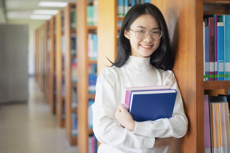 回到学校教育知识学院大学概念,拿着她的书的美丽的女性大学生愉快地微笑 库存图片