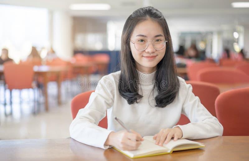 回到学校教育知识学院大学概念,拿着她的书的美丽的女性大学生愉快地微笑 免版税库存照片