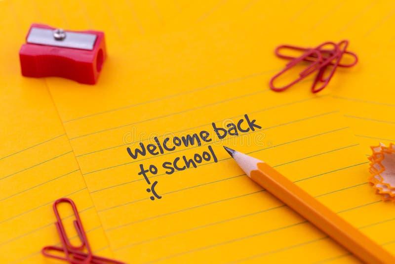 回到学校文具和橙色纸片在绿色校务委员会的谎言在铅笔和被弄皱的页附近 拷贝空间舱内甲板 库存图片