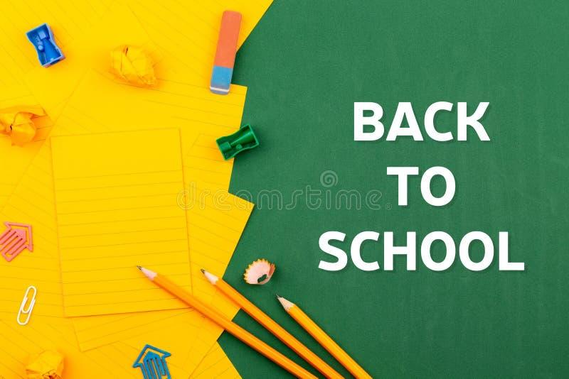 回到学校文具和橙色纸片在绿色校务委员会的谎言在铅笔和被弄皱的页附近 拷贝空间舱内甲板 免版税库存图片