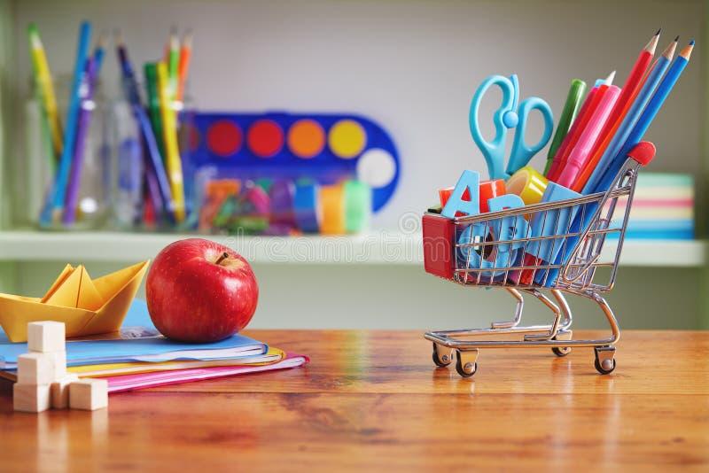 回到学校有供应的购物车在木表上 免版税库存照片