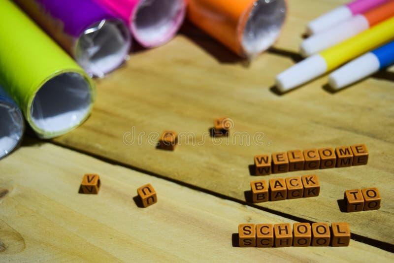 回到学校木立方体的与五颜六色的纸和笔,在木背景的概念启发的欢迎 库存照片