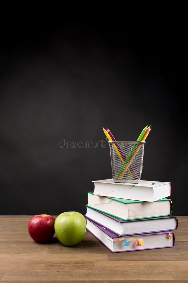 回到学校概念、被堆积的书、在黑黑板背景和红色和绿色苹果隔绝的上色铅笔 库存图片