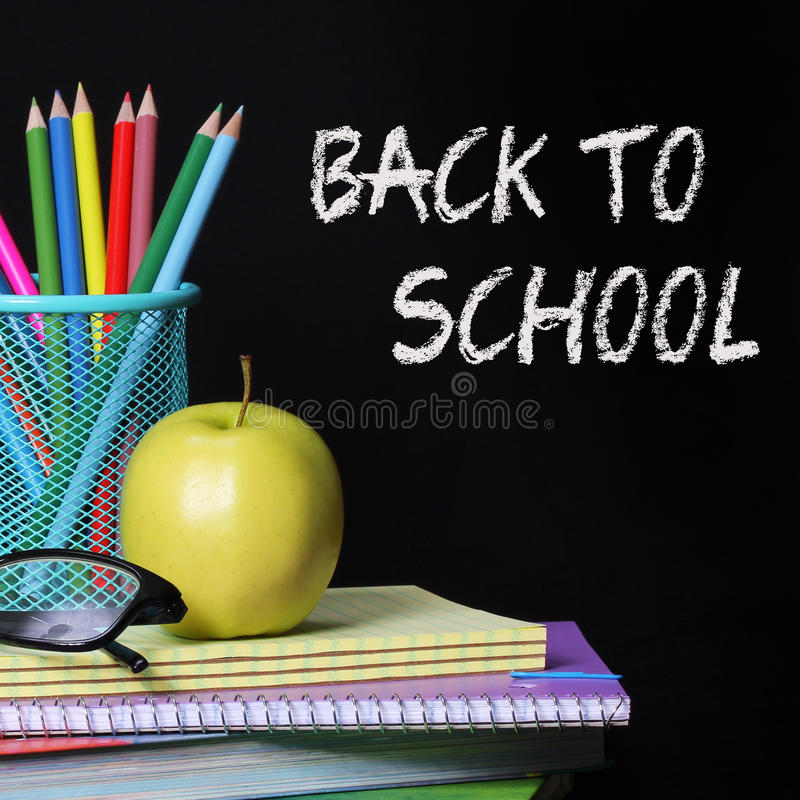 回到学校概念。一块苹果、色的铅笔和玻璃在堆书在黑背景 库存照片