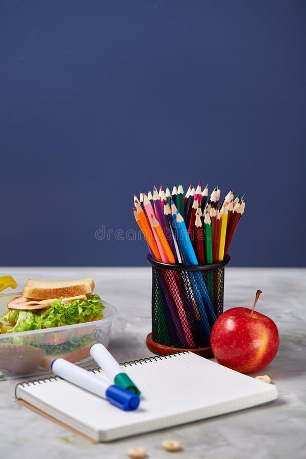 回到学校概念,学校用品,饼干,包装了午餐和饭盒在白色黑板,选择聚焦 免版税库存照片