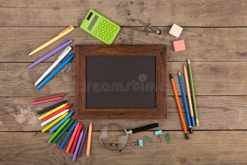 回到学校概念-在木书桌上的学校用品 免版税库存图片