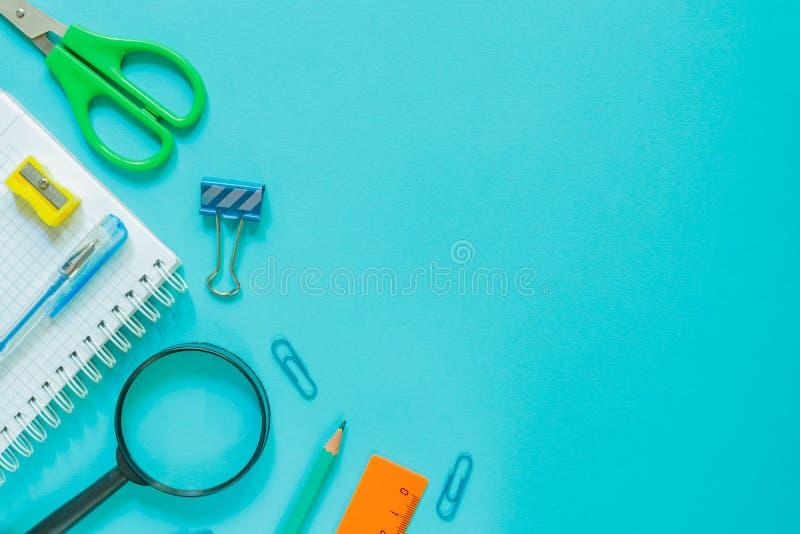 回到学校概念-在蓝色背景的学校办公室供应 您的设计的拷贝空间 库存图片