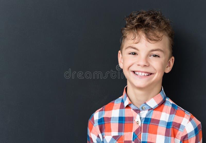 回到学校概念-看照相机的愉快的男孩 免版税库存图片
